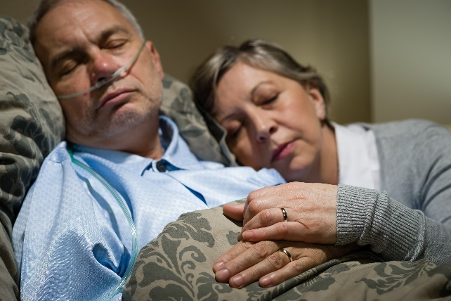 Protect your assets before entering into a nursing home: ill husband in bed with wife nursing him