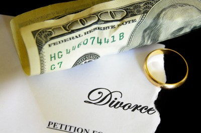 Divorce costs money. Picture of $100 American bill and a gold wedding ring.